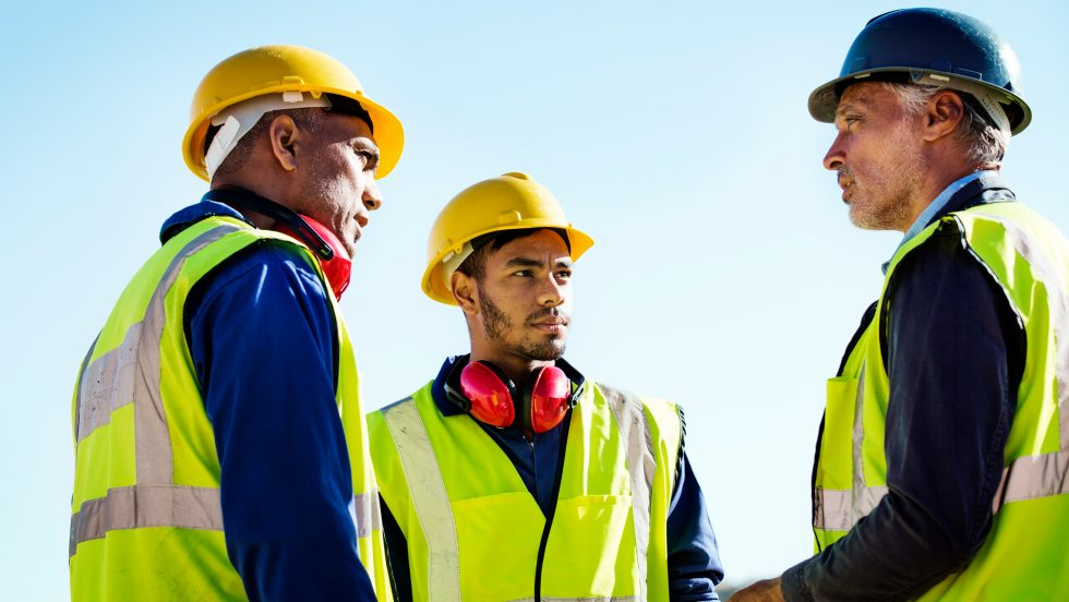 picture of three construction workers wearing yellow jackets